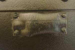Metalen plaatje aan de bovenzijde van de geldkast.